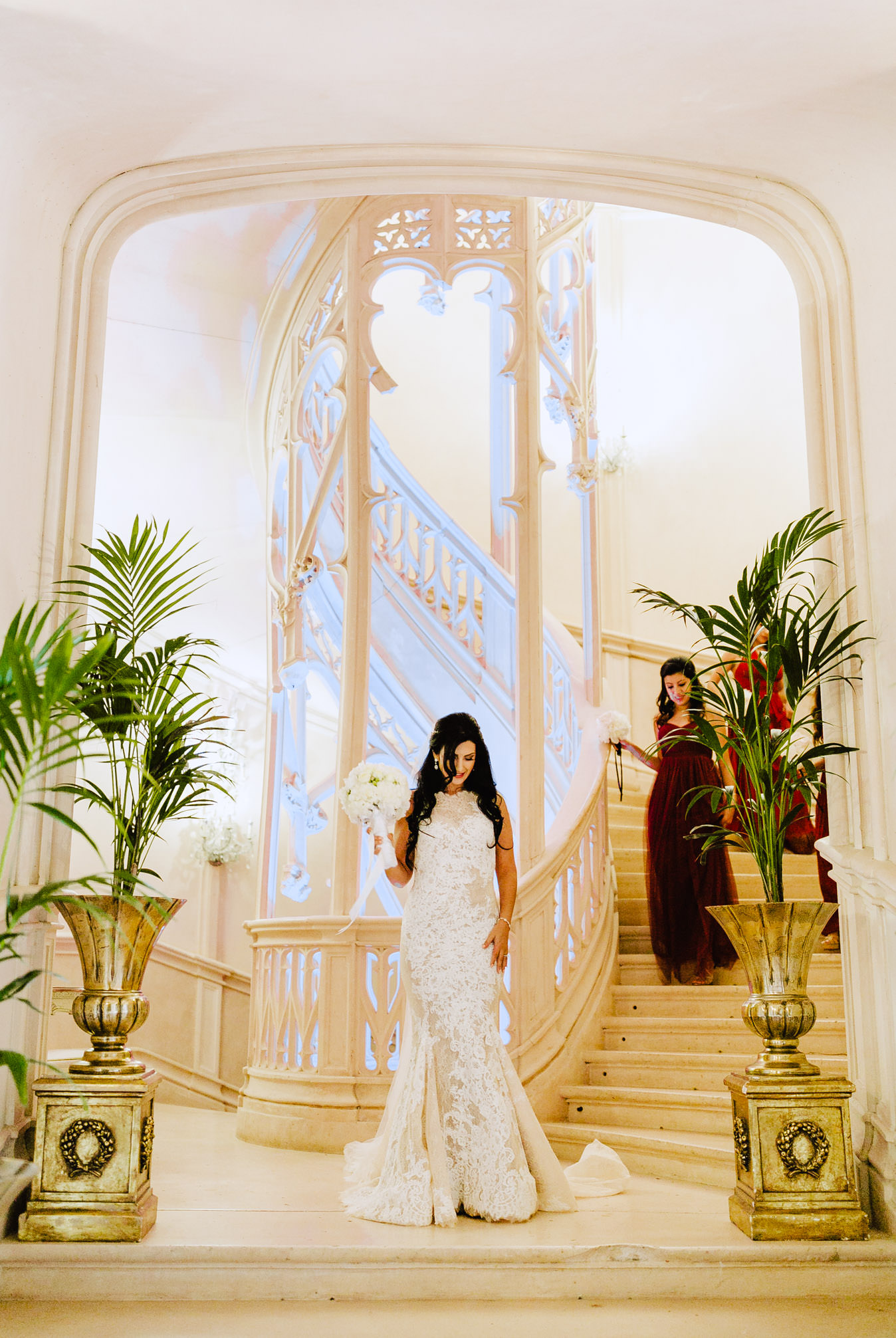 bride at the bottom of the main staircase in chateau challain wedding