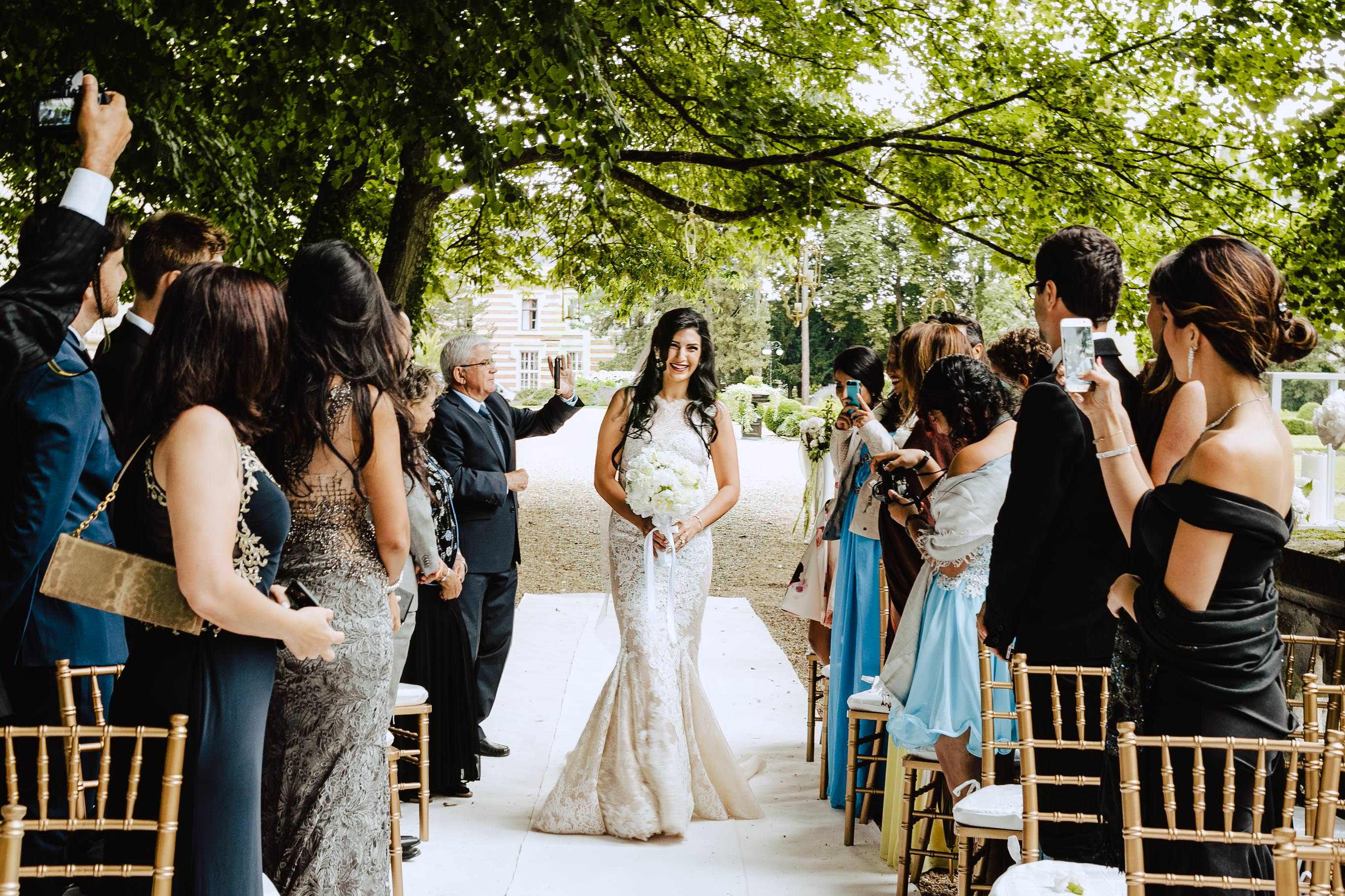 outdoor ceremony in chateau challain bride walking the isle